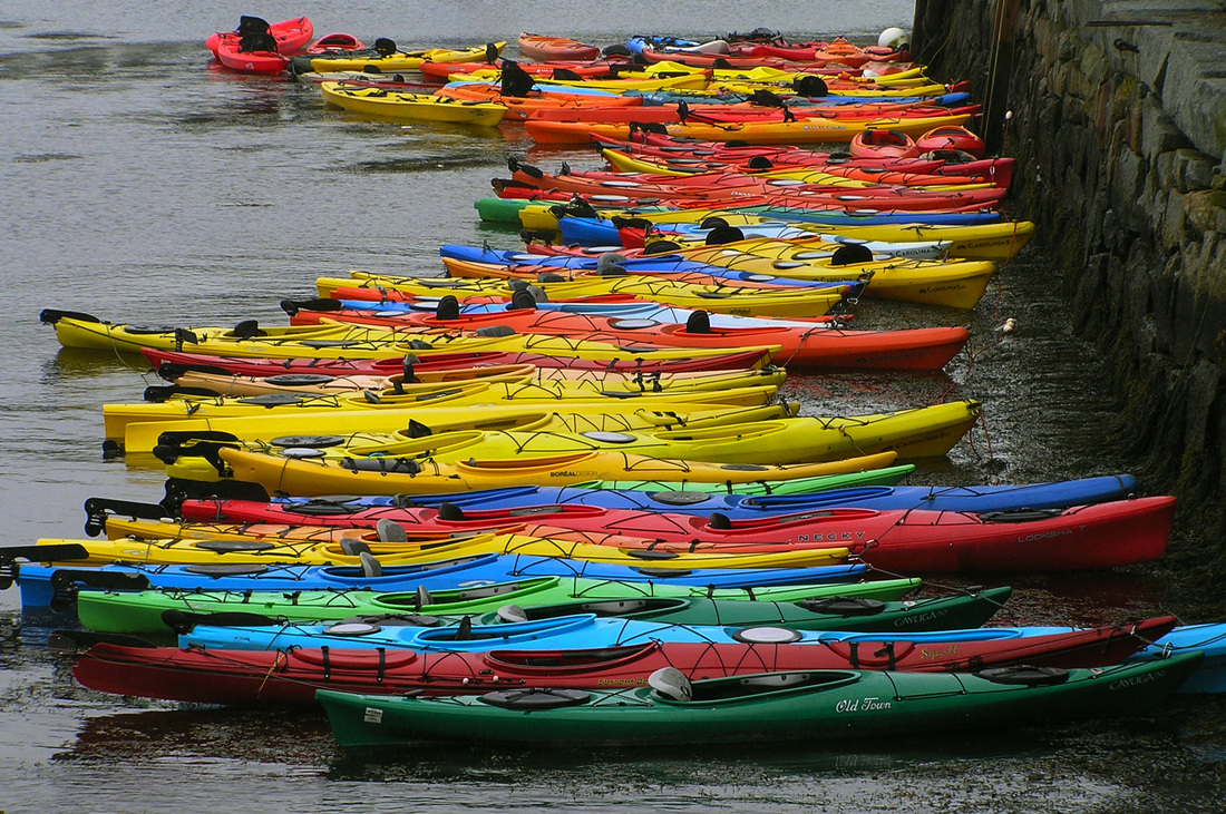 Photograph of colorful kayaks.