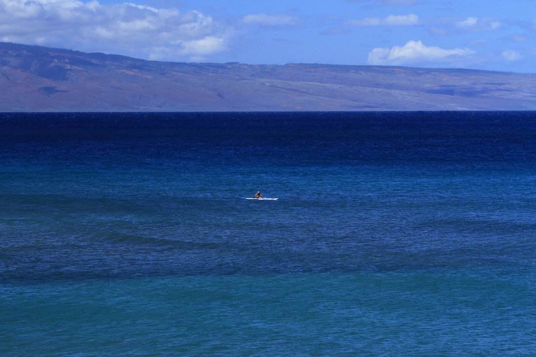 A photograph of a lone kayaker on the deep blue pacific ocean off Maui.